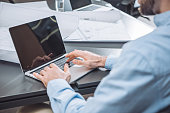 cropped shot of architect working with laptop at office