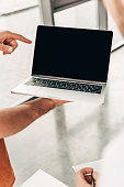 cropped shot of business people pointing at blank laptop screen during work