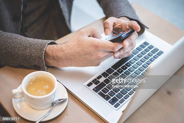 Cropped shot of businessman sitting in cafe texting on smartphone