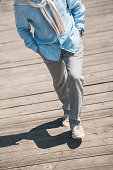 cropped shot of casual man walking by wooden pavement at daytime