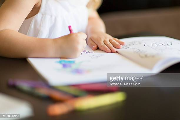 Cropped shot of girl coloring in book with crayons