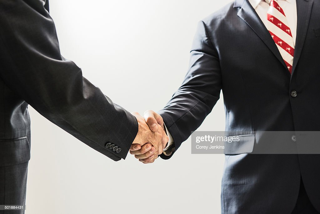 Cropped shot of male business lawyers shaking hands in office