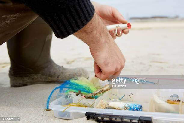 Cropped shot of male hand preparing fishing hook on beach