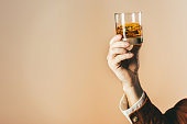 cropped shot of man holding glass of whiskey isolated on beige