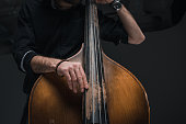 cropped shot of man playing contrabass on black