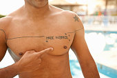 Cropped shot of man pointing to chest tattoo at hotel swimming pool, Rio De Janeiro, Brazil