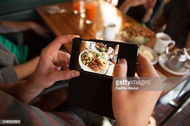 Cropped shot of man taking photograph of meal in vegetarian restaurant