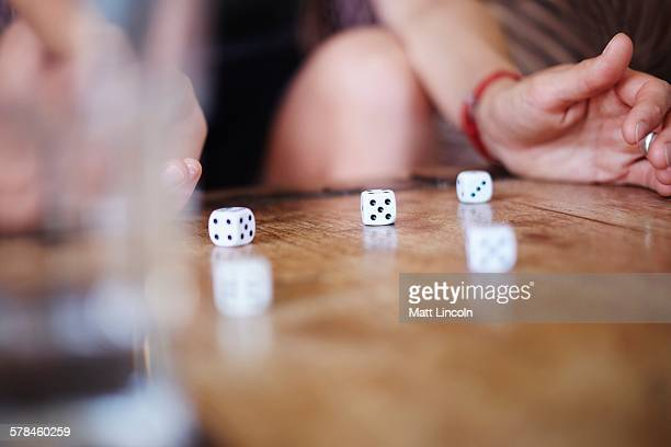 Cropped shot of mature woman playing with dice on table
