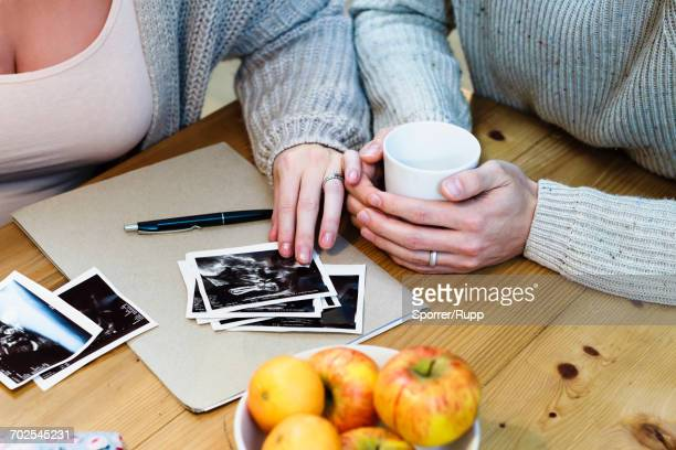 Cropped shot of pregnant couple looking at pregnancy scans on table