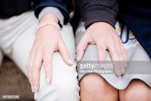 Cropped shot of romantic young couple with hands on each others knees