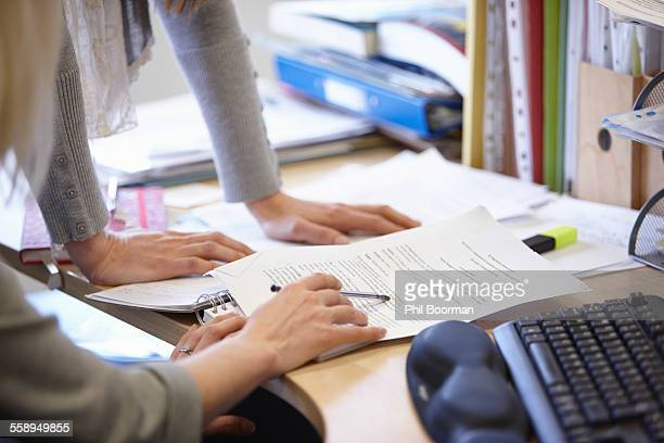 Cropped shot of two businesswomen checking paperwork at office desk
