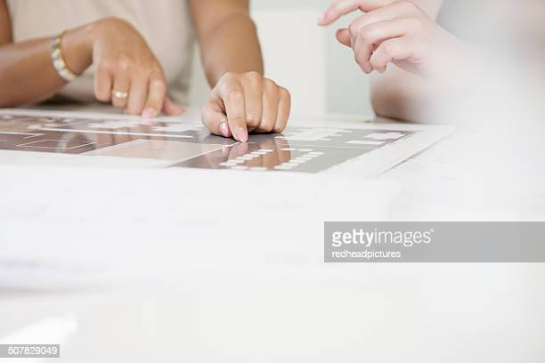 Cropped shot of two businesswomen's hands and blueprint