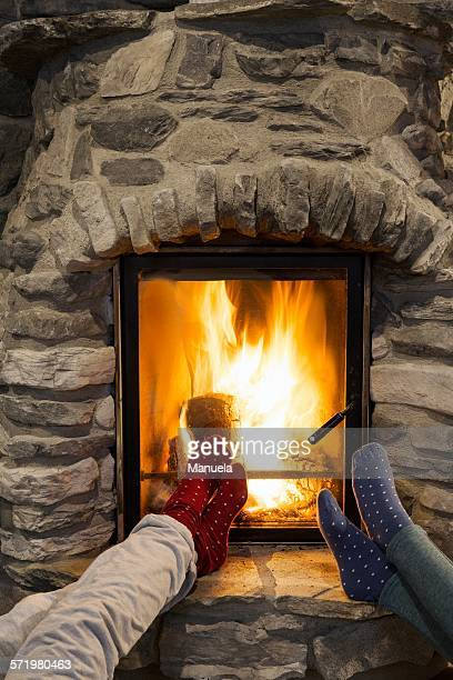 Cropped shot of two young women with feet up in front of fireplace