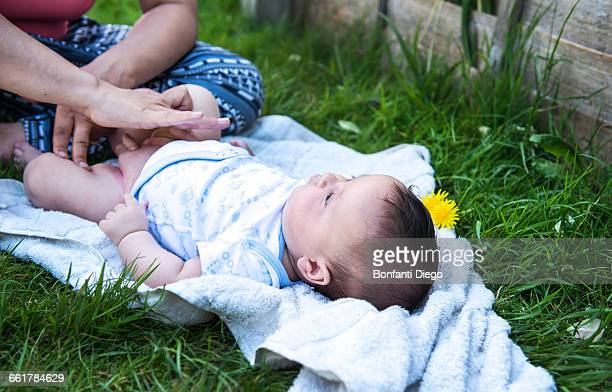 Cropped shot of woman applying cream whilst changing baby sons nappy in garden