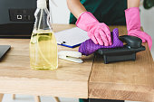 cropped shot of woman in rubber gloves cleaning telephone on table in office