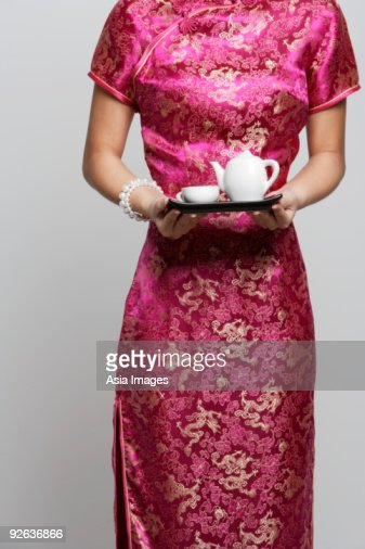 Cropped shot of woman wearing a pink cheongsam holding tea