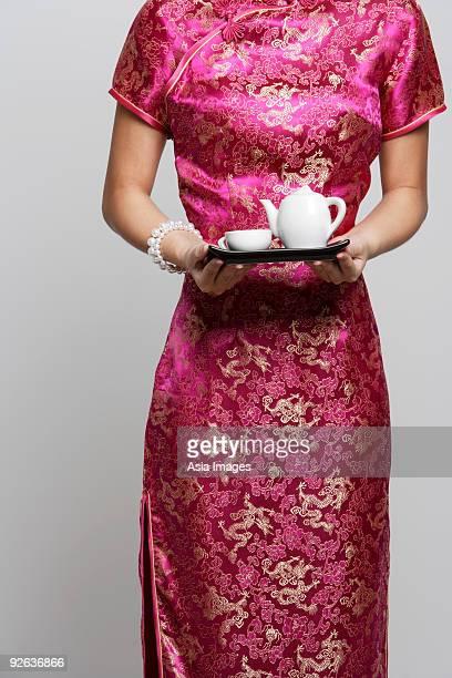 Cropped shot of woman wearing a pink cheongsam holding tea