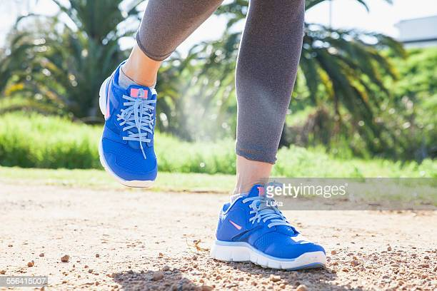 Cropped shot of womans legs running on dirt track in park