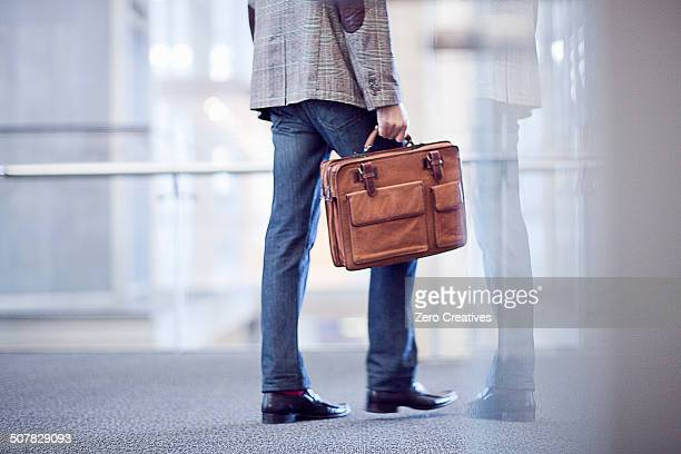 Cropped shot of young businessman with briefcase in conference centre