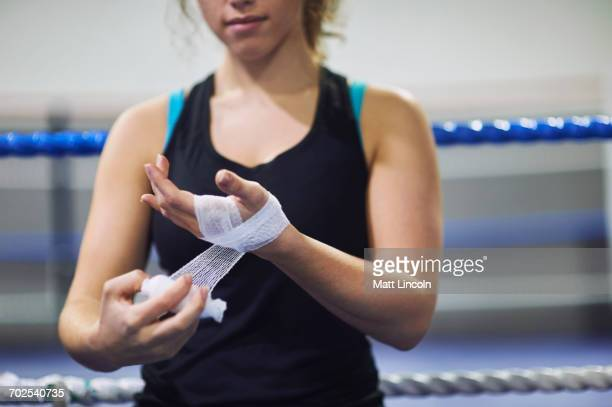 Cropped shot of young female boxer bandaging hands