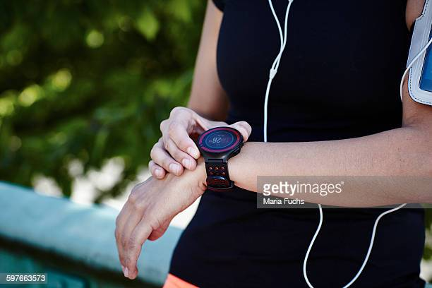 Cropped shot of young female runner setting smartwatch