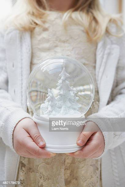 Cropped shot of young girl holding christmas snow globe