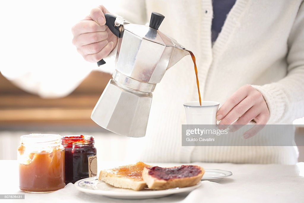 Cropped shot of young woman pouring coffee for breakfast