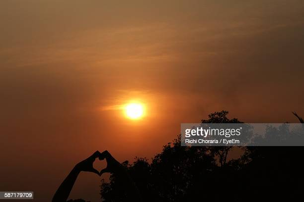 Cropped Silhouette Hands Making Heart Shape Against Sky During Sunset
