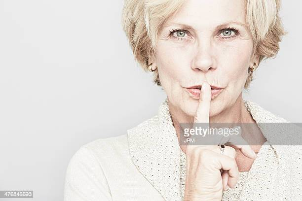 Cropped studio portrait of senior woman with finger on lips