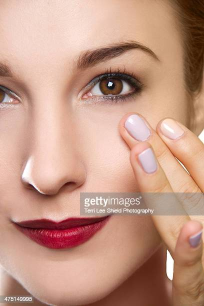 Cropped studio portrait of young woman touching her face