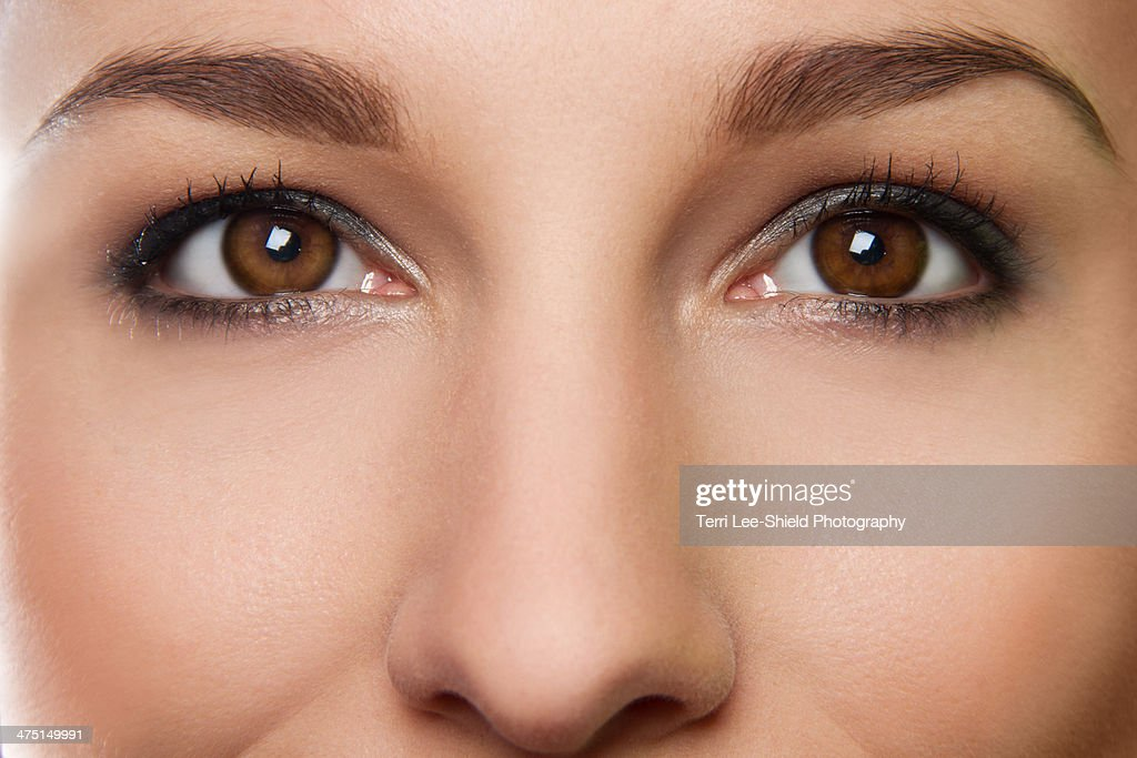 Cropped studio portrait of young woman's eyes