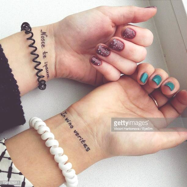 Cropped Tattooed Hands With Nail Polish And Bracelet