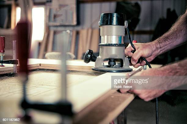 A cropped view of adult, male carpenter working with tools in his wood shop