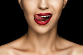 cropped view of beautiful woman licking lips with red lipstick, isolated on black