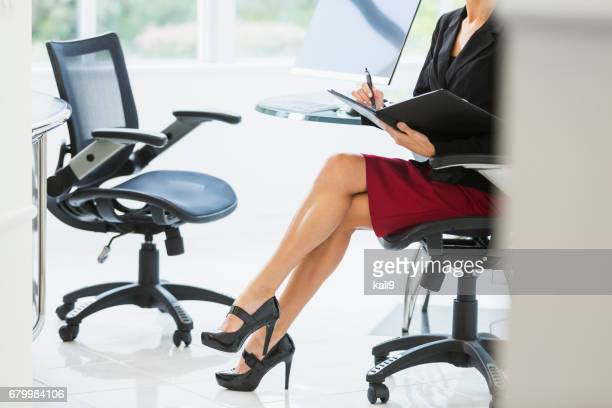 Cropped view of businesswoman in office taking notes