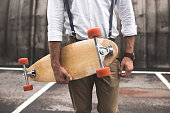 cropped view of fashionable man in white shirt and suspenders holding longboard