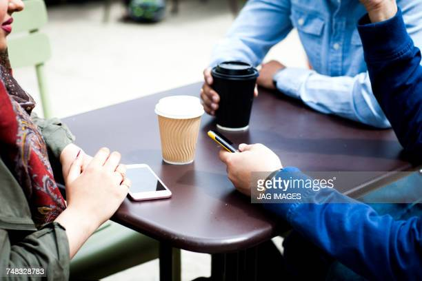 Cropped view of friends with smartphone having coffee together