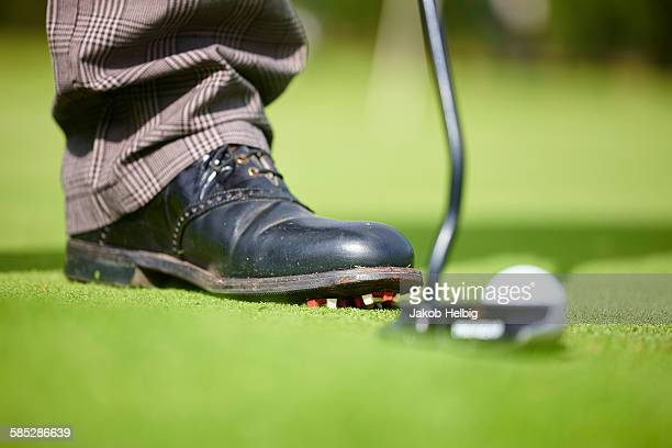 Cropped view of golfers foot wearing golf shoe, golf club and golf ball