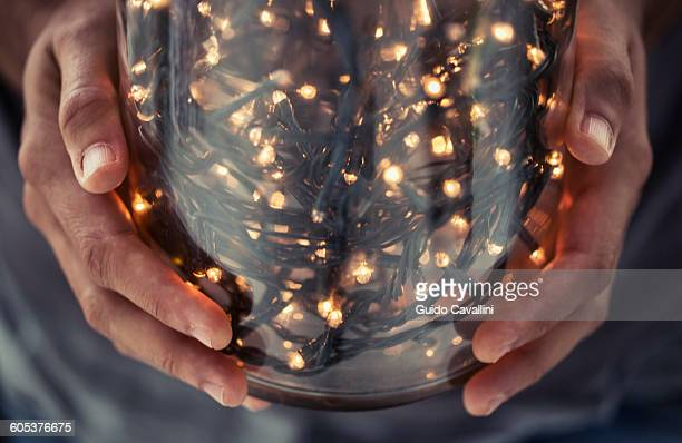 Cropped view of hands holding glass jar filled with decorative lights