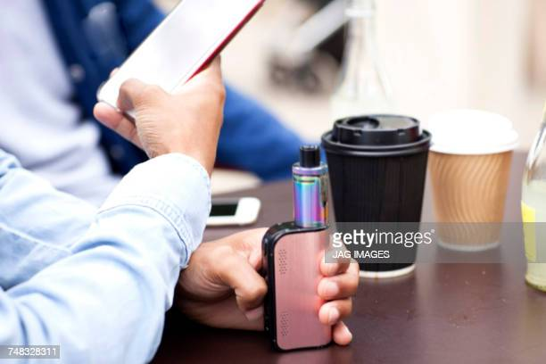 Cropped view of man holding smartphone and vape