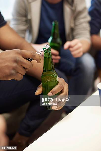 Cropped view of mans hands opening bottle of beer