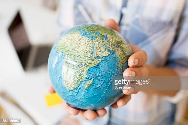 Cropped view of mature women hands holding small globe