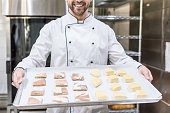cropped view of smiling cook holding baking tray with raw dough