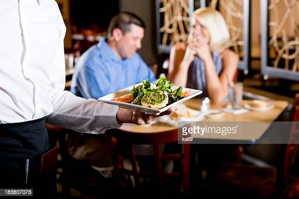 Cropped view of waiter holding salad plate in restaurant