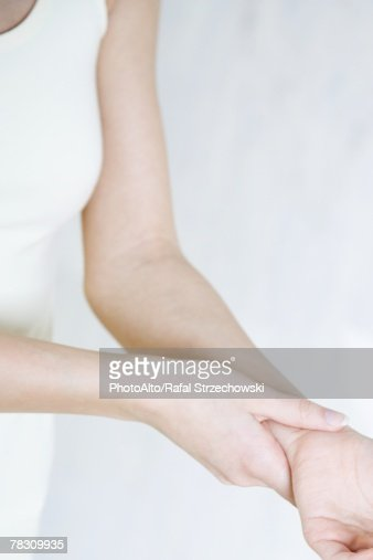 Cropped view of woman holding wrist, close-up