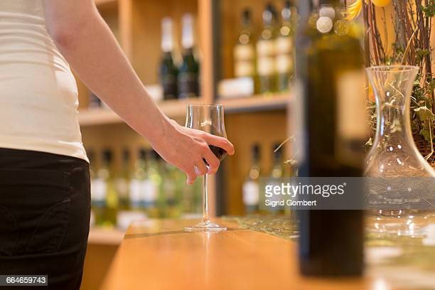 Cropped view of woman in wine shop holding glass of red wine