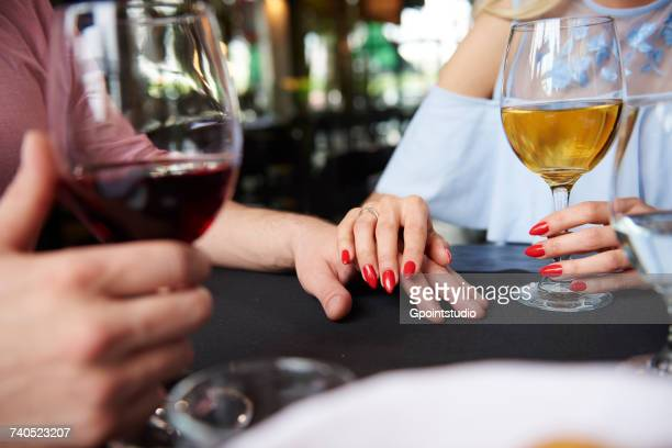 Cropped view of womans hand on boyfriends hand at restaurant table