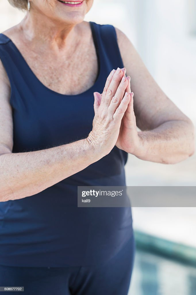 Cropped view, senior woman standing with palms together : Stockfoto
