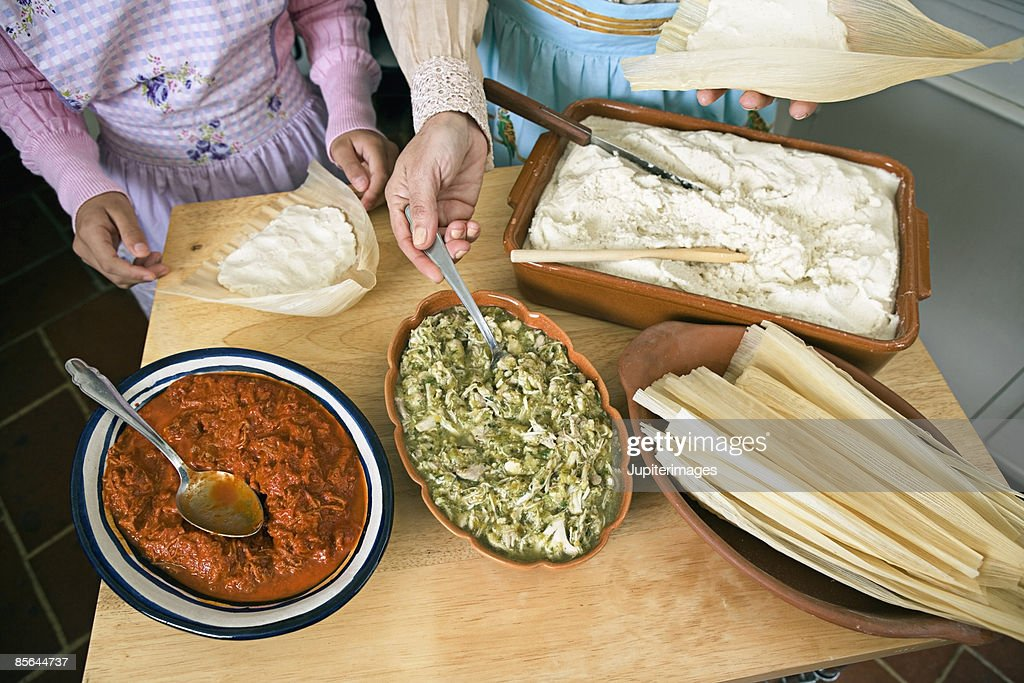 Cropped woman and girl preparing tamales