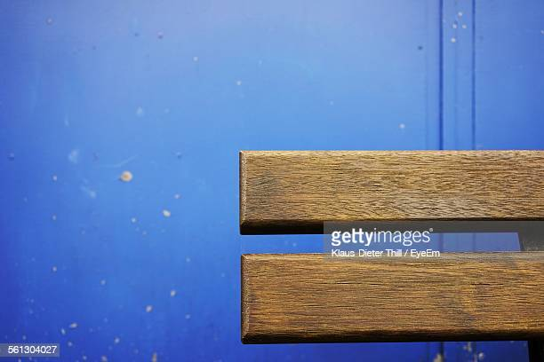 Cropped Wooden Bench Against Blue Wall